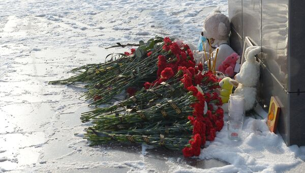 Цветы, свечи и детские игрушки фотографии самолета в центре Орска, принесенные в память о крушении Ан-148 Саратовских авиалиний. Архивное фото