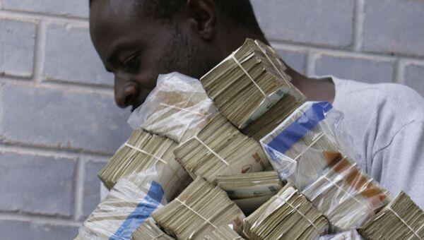 Мужчина несет пачки денег в Хараре, Зимбабве. 5 марта 2008