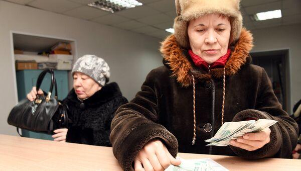 Женщина пересчитывает полученную пенсию на почтамте. Архивное фото