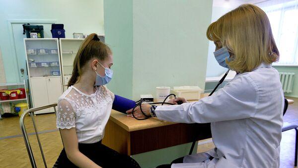 Врач осматривает пациента в целях профилактики заболевания гриппом и ОРВИ