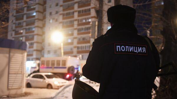 Сотрудник правоохранительных органов у одного из жилых домов на улице Авангардная в Казани, где 27 февраля произошла перестрелка
