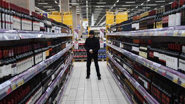 Покупатель в отделе алкогольной продукции в супермаркете