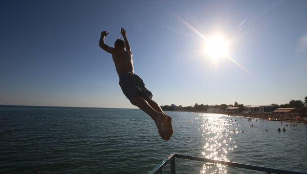 Прыжок в море с пирса на городском пляже Евпатории