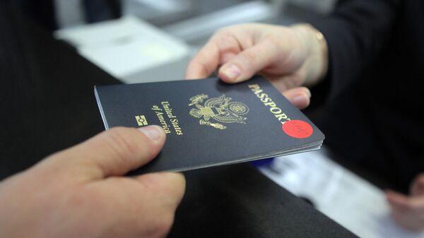 Пассажир предъявляет паспорт гражданина США на стойке регистрации в аэропорту города Сочи