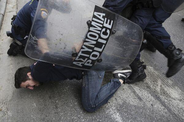 Полиция задерживает протестующего во время столкновений в центре Афин. 14 марта 2018 года