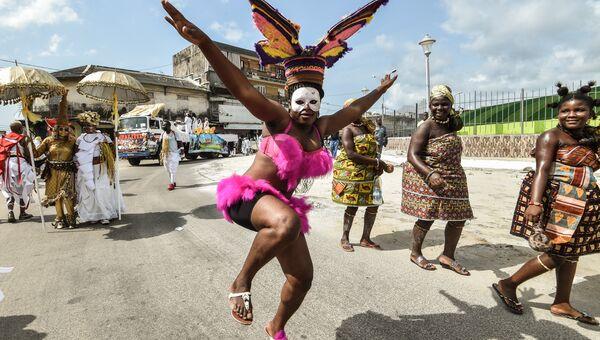 Члены афро-американской группы Jouvay Fest танцуют на параде в Абиджане