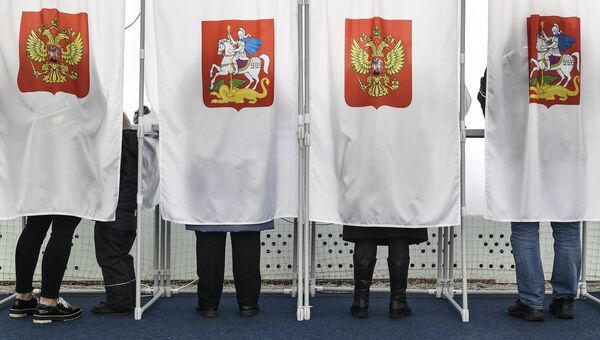 Избиратели во время голосования на выборах на избирательном участке №13-06 в Москве. Архивное фото