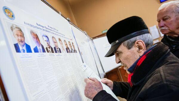 Мужчины у стенда с информацией о кандидатах в президенты РФ