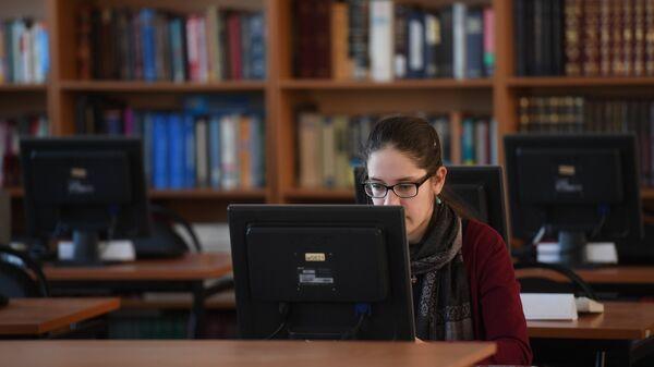 Девушка сидит за компьютером в библиотеке