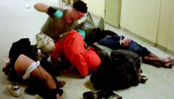 Американский военный избивает заключенных в тюрьме Абу-Грейб в Багдаде, Ирак. 2003