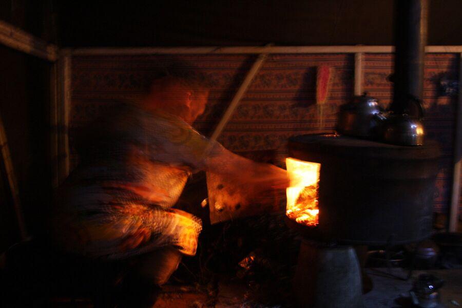 Женщина топит печь в палатке, полуостров Канин, Ненецкий автономный округ