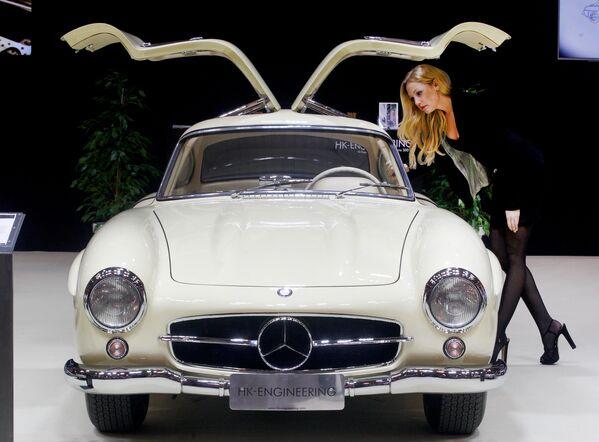Девушка рядом с автомобилем Mercedes-Benz 300 SL Coupe 1956 года на выставке Techno-Classica Essen в Германии