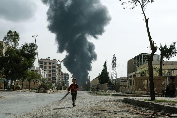 Мальчик бежит по улице в городе Дума, Сирия. 20 марта 2018 года