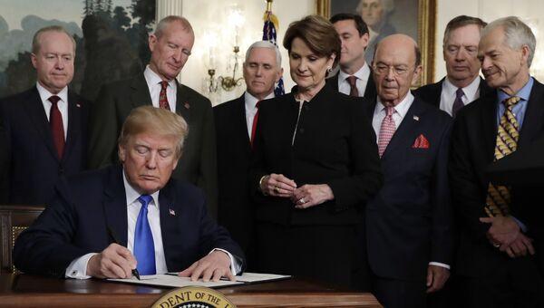 Президент США Дональд Трамп подписывает президентский меморандум, устанавливающий тарифы и инвестиционные ограничения для Китая. 22 марта 2018