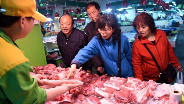 Покупатели выбирают свинину в супермаркете в Ханчжоу, Китай