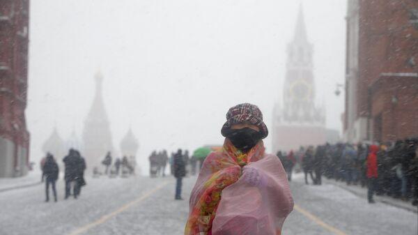 Туристка во время снегопада на Красной площади в Москве.