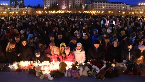 Участники акции на площади Ленина в Чите зажигают свечи в память о погибших при пожаре в торговом центре Зимняя вишня в Кемерово
