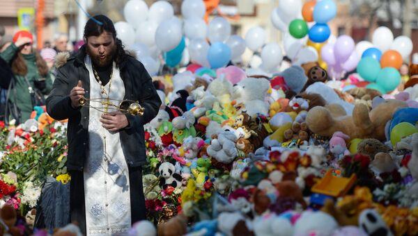 Священнослужитель у мемориала из цветов и воздушных шаров в память о жертвах пожара в торгово-развлекательном центре Зимняя вишня в Кемерово