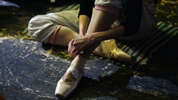 Балерина завязывает пуанты.