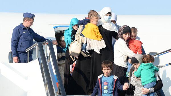 Дети и родители, возвращенные из Сирии, выходят из самолета в аэропорту Грозного