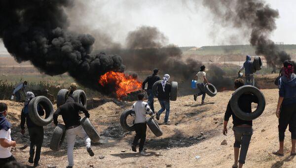 Палестинские протестующие во время столкновений с израильскими военными на границе сектора Газа и Израиля. Архивное фото