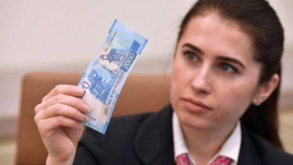 Девушка с купюрой 2000 рублей. Архивное фото
