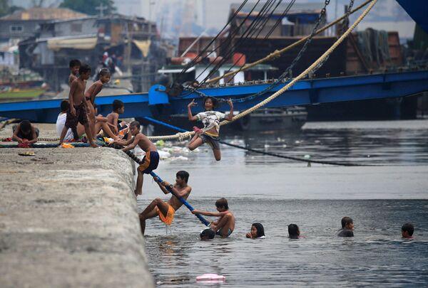 Дети купаются в Манильском заливе во время жаркой погоды на Филиппинах