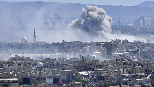 Горящие дома в пригороде Дамаска у лагеря палестинских беженцев Ярмук. Архивное фото