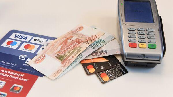 Терминал оплаты банковскими картами и денежные купюры. Архивное фото