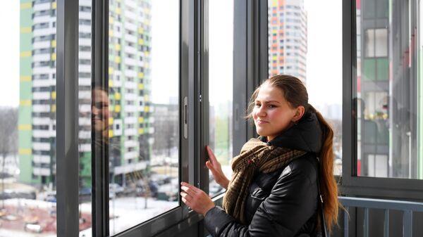 Девушка на лоджии новой квартиры
