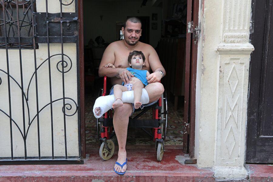 Кубинец с ребенком на улице в районе Старая Гавана