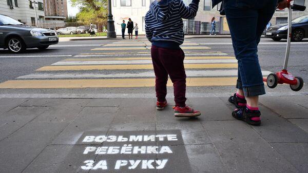 Предупреждающая надпись для пешеходов, нанесенная на асфальте перед переходом