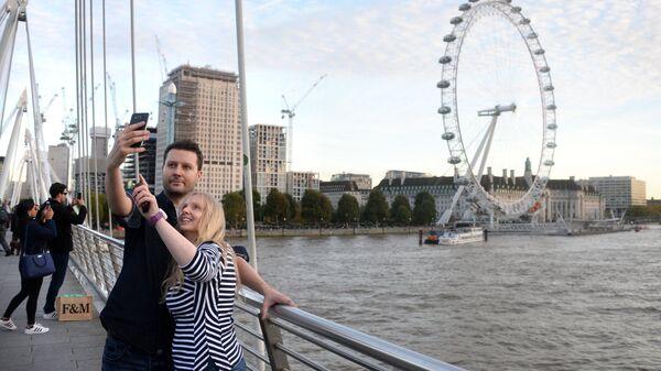 Туристы фотографируются на фоне Колеса обозрения Лондонский глаз на берегу Темзы в Лондоне