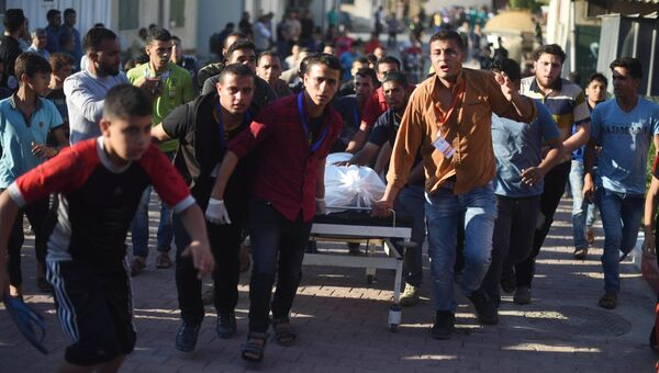 Палестинцы везут пострадавшего в столкновениях с израильскими военными на границе сектора Газа и Израиля