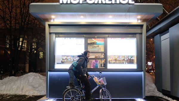 Велосипедист у киоска продажи мороженого на улице Москвы