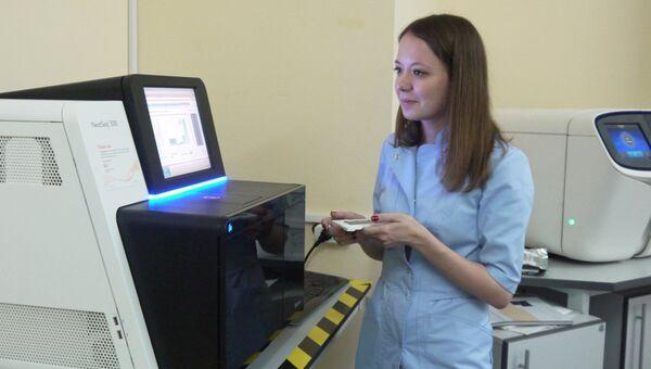 Научный сотрудник лаборатории ДНК-диагностики МГНЦ Ольга Миронович запускает секвенатор нового поколения
