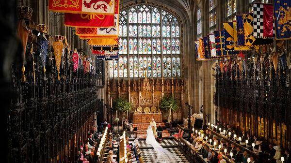 Британский принц Гарри и Меган Маркл во время свадебной церемонии в часовне Св. Георгия в Виндзорском замке недалеко от Лондона, Англия. 19 мая 2018