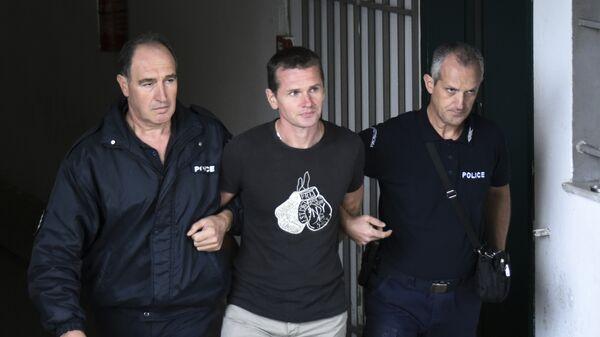 Полицейские сопровождают Александра Винника в греческом городе Салоники. Архивное фото