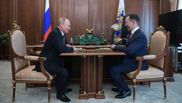 Владимир Путин и бывший глава города Якутска Айсен Николаев во время встречи. 28 мая 2018