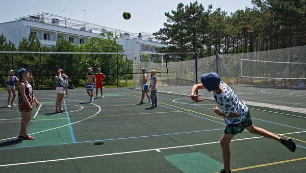 Дети играют в пионербол на спортивной площадке детского оздоровительного лагеря Бригантина в поселке Песчаное в Крыму