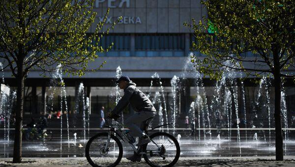 Мужчина катается на велосипеде в парке Музеон в Москве