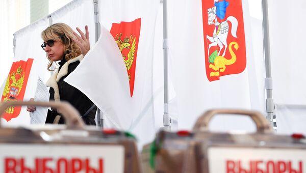 Девушка во время голосования на избирательном участке в Москве. Архивное фото