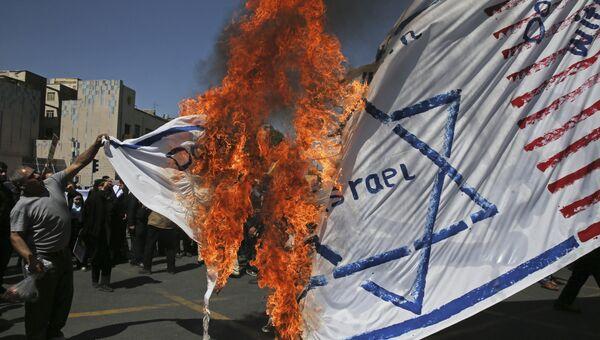 Иранские демонстранты сжигают изображение американского и израильского флагов во время ежегодной антиизраильской демонтсрации на день Аль-Кудс в Тегеране, Иран. 8 июня 2018