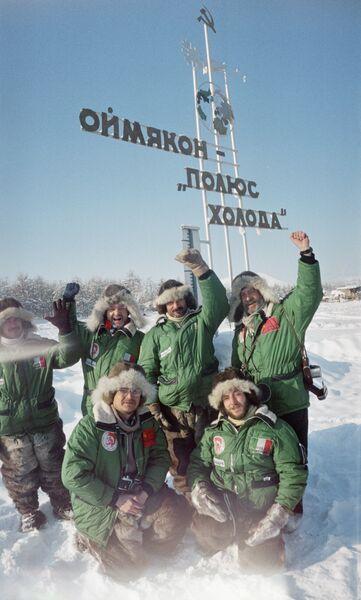 Туристы стоят у памятного знака Оймякон - полюс холода
