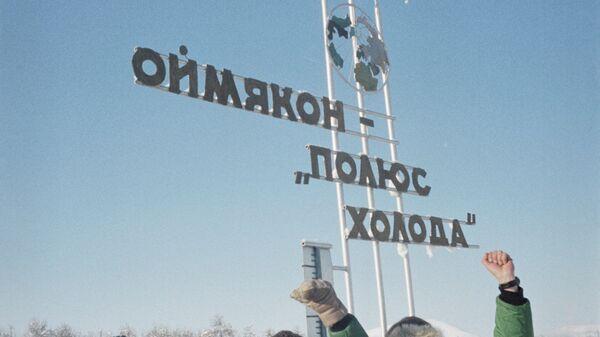 Туристы стоят у памятного знака Оймякон — полюс холода