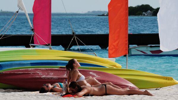 Отдыхающие на пляже одного из Мальдивских островов