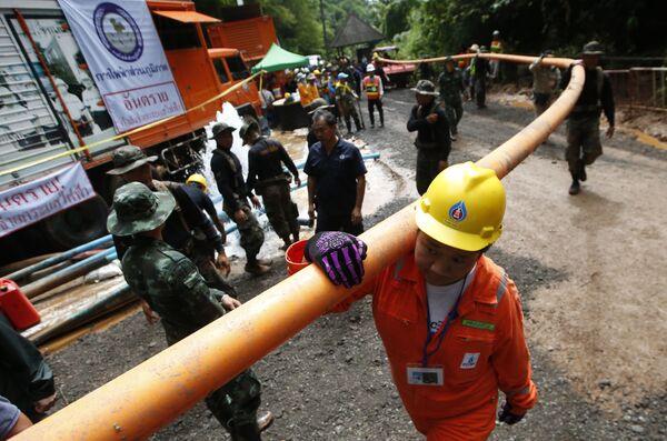 Рабочий держит трубу для откачки воды из пещеры Тхам Луанг в провинции Чиангмай