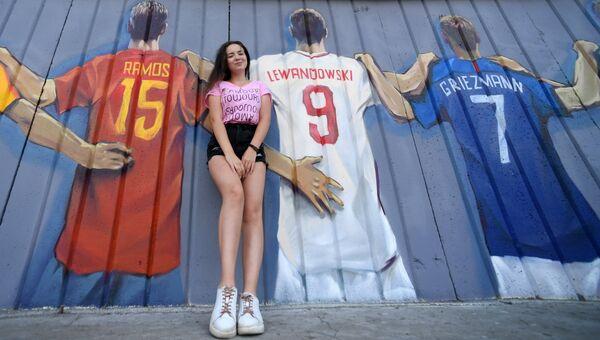 Девушка на фоне граффити с изображение игроков всех сборных чемпионата мира по футболу 2018