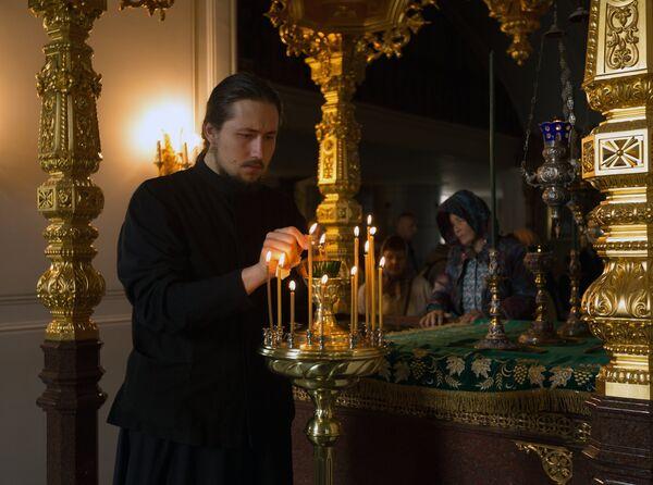 Монах зажигает лампады у раки с мощами святых Сергия и Германа в день празднования памяти преподобных Сергия и Германа Валаамских