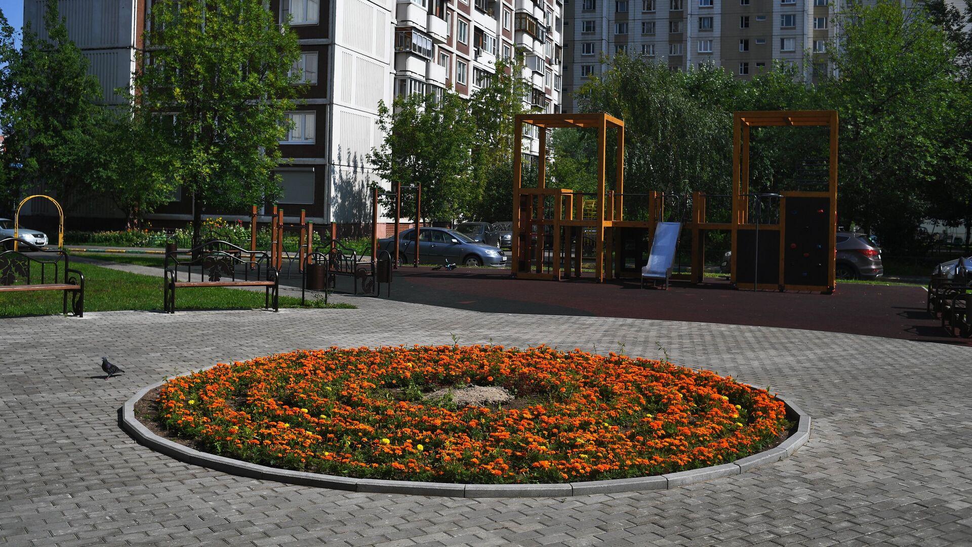 Детская игровая площадка и цветочная клумба во дворе дома в Москве - РИА Новости, 1920, 13.04.2021